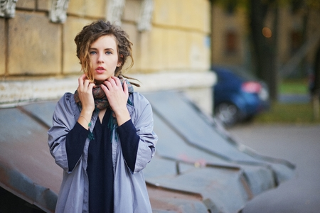 corrects: Very young woman standing near the house, and corrects a beautiful scarf around his neck Stock Photo