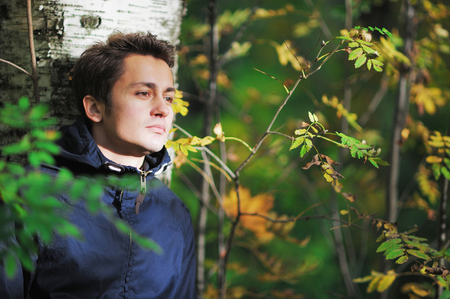 birchbark: Young brown-eyed man with a sad face leaned against the birch tree and sad looking to the side in autumn forest in Sunny day.
