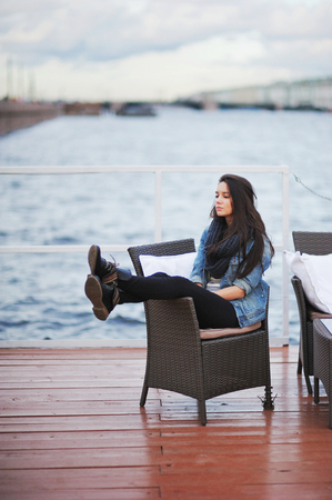 Beautiful brunette in a blue denim jacket and a black scarf sitting in a chair on the pier, with downcast eyes, on the background the blurred outlines of bridge and building in St. Petersburg.