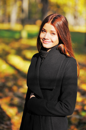 leafed: Cute smiling, brown-eyed girl with long brown hair in a black coat autumn park.