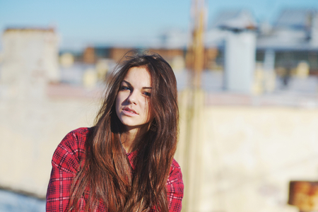 red plaid: Beautiful brunette girl with long shiny hair with blue eyes in a red plaid shirt on the background of the city roofs.