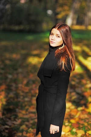 Gorgeous portrait of a young brown-haired woman outdoors in park in autumn.