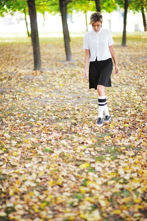 saddened: Pensive young girl goes on autumn Park with his head down.