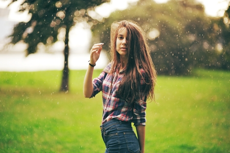warm shirt: a Young beautiful girl with long hair in a plaid shirt walks in the Park under a warm summer rain.