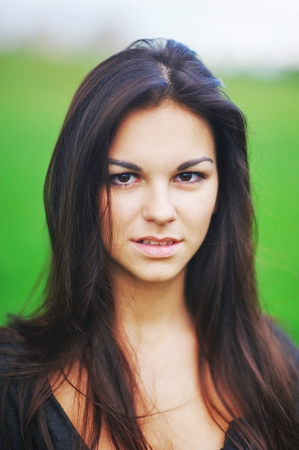 green brown: Portrait of gorgeous young woman with long hair and beautiful brown eyes on blurred green background, closeup Stock Photo