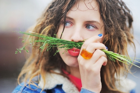 Young funny girl with dreadlocks poses a grimace, putting a tuft of grass on the lips, outdoors, close-up.