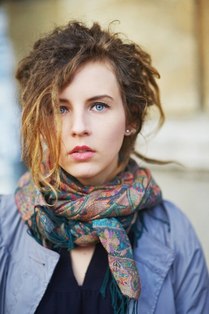 fair complexion: Portrait of charming girl with dreadlocks in her cloak and scarf on the neck on a city street.