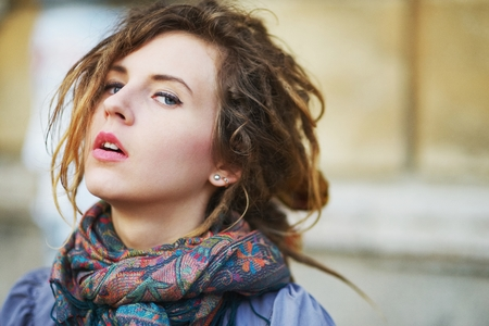 fair complexion: Portrait of cute girl with dreadlocks wearing a scarf on neck on the background wall of the house, closeup. Stock Photo