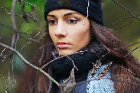 Beautiful pensive woman with brown eyes wearing a scarf and a hat in the Park among the bare branches of trees Stock Photo