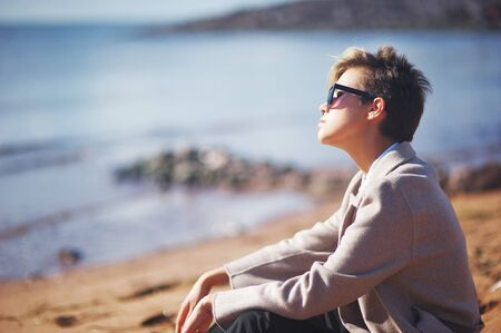 sullenly: Dreamy stylish girl in fashion clothing and dark glasses sitting on the rocks under the rays of the autumn sun. Stock Photo