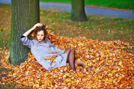 Pretty girl in a light purple cloak, with downcast eyes lying on a pile of fallen autumn leaves in the forest, leaning his head against the tree. Stock Photo
