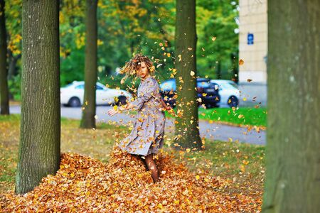 Cute attractive girl whirls and throws leaves in the air, on the walk around the house a clear autumn day. Stock Photo