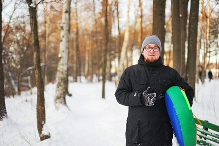 tubing: A young bearded guy in glasses goes with the tubing in the winter woods.