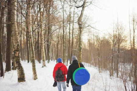 tubing: Two young men with a backpack and go tubing in the winter woods
