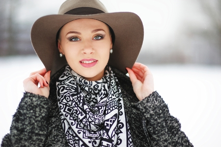 Magnificent portrait of young beautiful girl with a hat in winter Park, closeup. Stock Photo