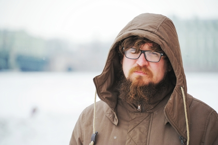 Portrait of pensive young man in glasses and a jacket with a hood in the town square on a winter day