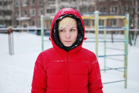 A young girl in a red hooded jacket stands in a St. Petersburg yard in the Playground, snowflakes falling on her face and melt. Stock Photo
