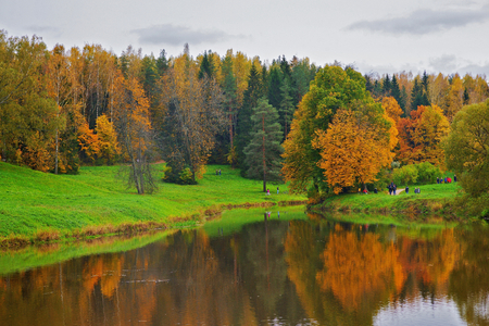 RUSSIA. PAVLOVSK. OCT. 2016. Colorful trees around clear lake in a suburban Park of Saint-Petersburg in autumn.