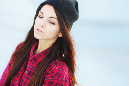 Beautiful long haired brunette girl with a lowered gaze in a red plaid shirt and black hat posing in a cool autumn day, close up. Stock Photo