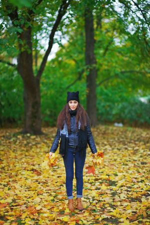 Young beautiful long-haired brunette with maple leaves in hands in autumn Park.