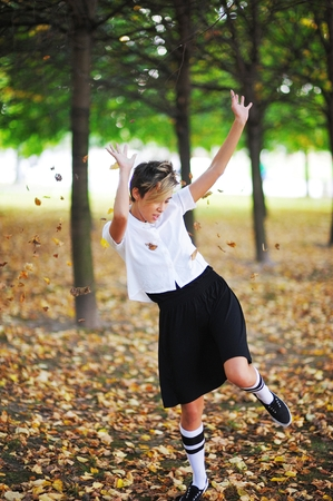 Cute young girl dancing and throwing leaves in the air in the autumn park Stock Photo
