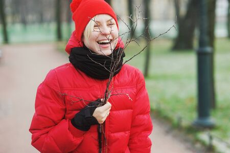 Portrait of fun laughing blonde in red jacket and hat with tree branches hand on a walk in the Park. Stock Photo