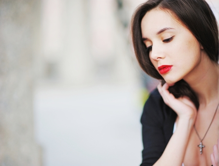 red cardigan: beautiful girl with long hair in a white shirt and a black cardigan looking with painted red lipstick lips