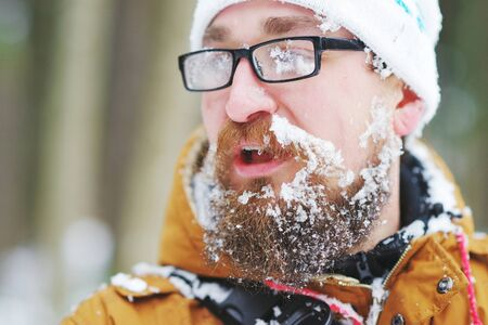 A young bearded man with glasses, covered in snow, something speaks during a journey in the winter forest.