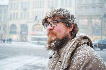 Interesting young bearded man in a coat and glasses walks in St. Petersburg during a snowfall.