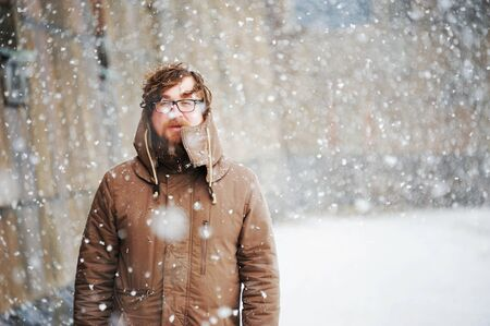 big man with a beard and glasses in winter clothes enjoys the snow, cold, snowfall, blizzard