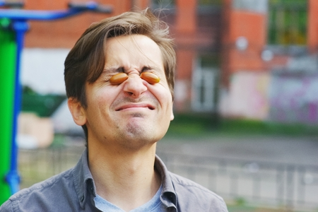 Young funny guy having fun by putting two acorns in the eyes, on the Playground in the yard Stock Photo
