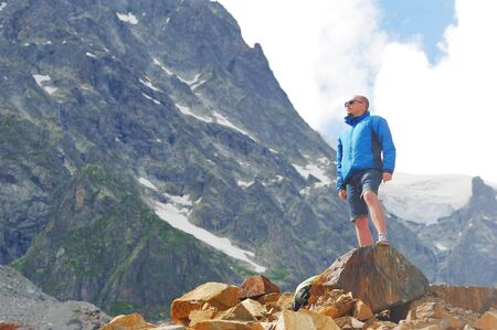 blue background: Young tourist in sunglasses, shorts, blue jacket stands on edge of cliff, admiring mountain scenery on background of snow-capped peaks, floating in sky clouds. Sport and the concept of healthy lifestyle