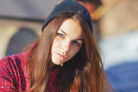 Portrait of a beautiful serious teen girl with blue eyes, wearing a red shirt and hat.