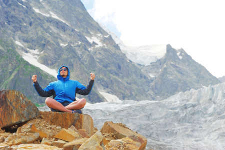 blue background: Young man in sunglasses and blue jacket with hood sitting on edge of cliff in pose of Lotus with their hands up, against background of snow-capped peaks. Sport and concept of a healthy lifestyle. Stock Photo