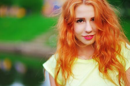 A wonderful portrait of a beautiful young woman with red hair and bright makeup outdoors in the summer.