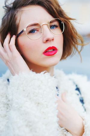Young beautiful short-sighted girl in a white jacket stares through his glasses at a city street, close-up.