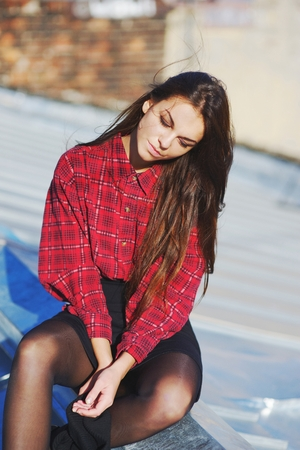 Young long-haired brunette girl in red plaid shirt and short skirt sitting on the roof with my eyes closed on a bright Sunny day.
