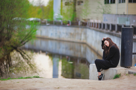 head down: Young sad girl sitting on a concrete slab near the canal, head down.