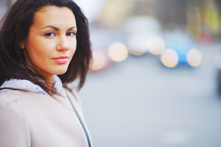 Portrait of young beautiful brown-eyed women brunettes on beautiful blurred background moving cars with headlights closeup