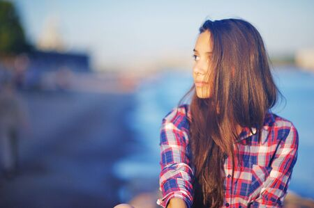 beautiful brunette girl in plaid shirt sitting on the embankment near the river