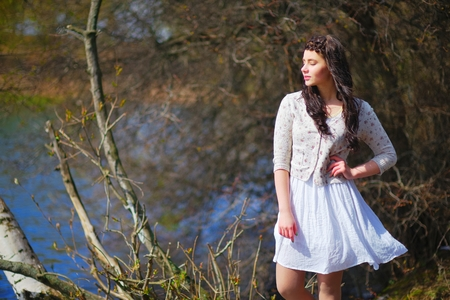 Wonderful portrait of a dreamy beautiful woman with silky hair, braided in a pigtail, in a white dress and jacket, meditating on the lake with my eyes closed, against the background of bare branches Stock Photo