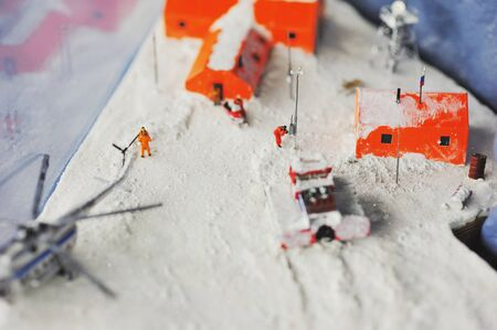 scenes from the life of the helicopter brought the repairmen on the Russian polar station. The orange houses on the background of white snow, in miniature
