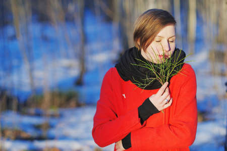 Portrait of beautiful woman with closed eyes in a red coat with a green twig in the hands, cold weather in a snowy forest. Stock Photo