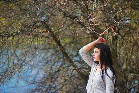 modesty: Wonderful portrait of beautiful long-haired girl with silky hair, braided in pigtail, a light sweater, meditating on the shore of lake, placing his hand on head, background of branches with blossoming buds Stock Photo