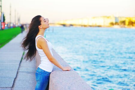 Beautiful portrait in profile cute beautiful brunette woman with long hair, fluttering in the wind, on the waterfront on blurred background of the urban landscape, close-up.