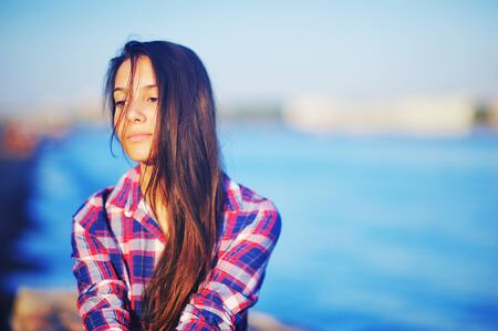 Young attractive brunette girl in red-and-blue plaid shirt shredded by the wind long hair with a wistful glance in the sunset on blurred background blue waters of river. Stock Photo