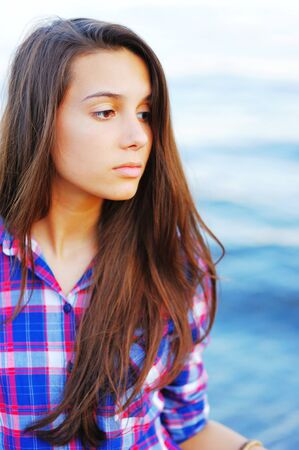 Young pretty brunette girl in red-and-blue plaid shirt with scattered over her shoulders long hair with a thoughtful look on blurred background blue waters of the sea. Stock Photo