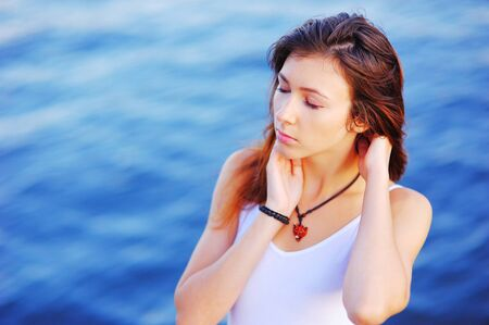 Gorgeous portrait of a young serene girl with long hair with closed eyes on a blurred background of blue waters of the sea.
