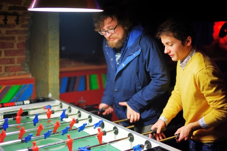 Two young men in evening bar play kicker. A friend with a beard, and the other in the yellow jacket. They are concentrated.