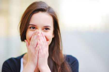 young beautiful girl covering her mouth with his hands for joy Stock Photo